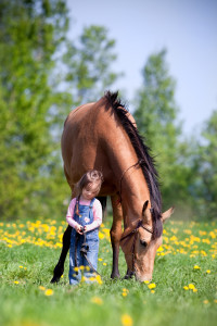 Child and bay Trakehner horse standing together